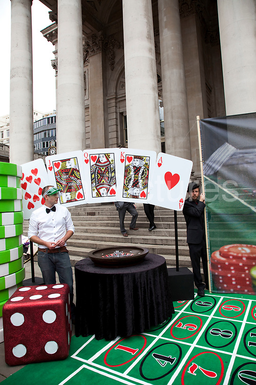 Robin Hood Tax supporters protest near the Bank of England in the City of London. Campaigners today set up a giant roulette table in the City of London to protest against bankers' taking risky bets and lining their pockets with billions in a game where taxpayers had to bail them out when things went wrong. The giant casino board, complete with chips, roulette wheel and image from renowned artist Peter Kennard was in front of the Royal Exchange in the City from 12pm. Casino bankers' placed multi-billion pound bets in a game they were guaranteed to win. The tax would apply to speculative trade on financial products: stocks, bonds commodities and currency transactions. The Robin Hood Tax is a tiny tax of 0.05% on banks' financial transactions. Introduced globally, it would raise hundreds of billions of pounds every year for good causes.
