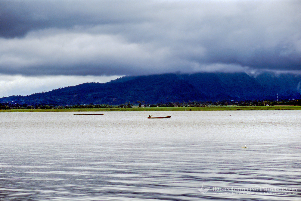 Indonesia, Sulawesi, Tondano. Lake Tondano is a large lake along the side of an ancient volcanic caldera. The shallow lake is a popular resort area. A small boat and fisherman.