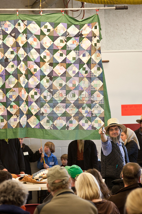 Amish auctioneer takes bids on handmade quilts during the Annual Mud Sale to support the Fire Department  in Gordonville, PA.