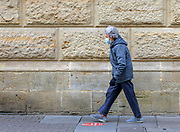 23rd February, Cheltenham, England. A shopper walks past Lloyds Bank in Cheltenham during the third national lockdown in England.
