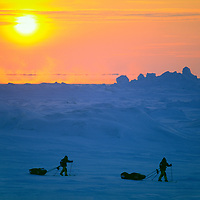 Reinhold & Hubert Messner test sleds amidst pressure ridges before attempting to cross the Arctic Ocean from Severnaya Zemlya, Russia, to Canada, via the North Pole. Background mist rises from open water leads. Temperature is about minus 35 degrees F.