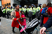 A woman pushes a pram with her daughter past riot police lines outside Topshop on Oxford Street. Anti capitalists / anarchists go on the rampage through central London on the back of the peaceful TUC protest march. The masked demonstrators ran a twisting route through the capital confusing the police and creating a situation which was very difficult to manage. The protesters attacked banks, shops and hotels, and the police in riot gear fought  face to face with them as they were pelted with ammonia, paint and fireworks loaded with coins.