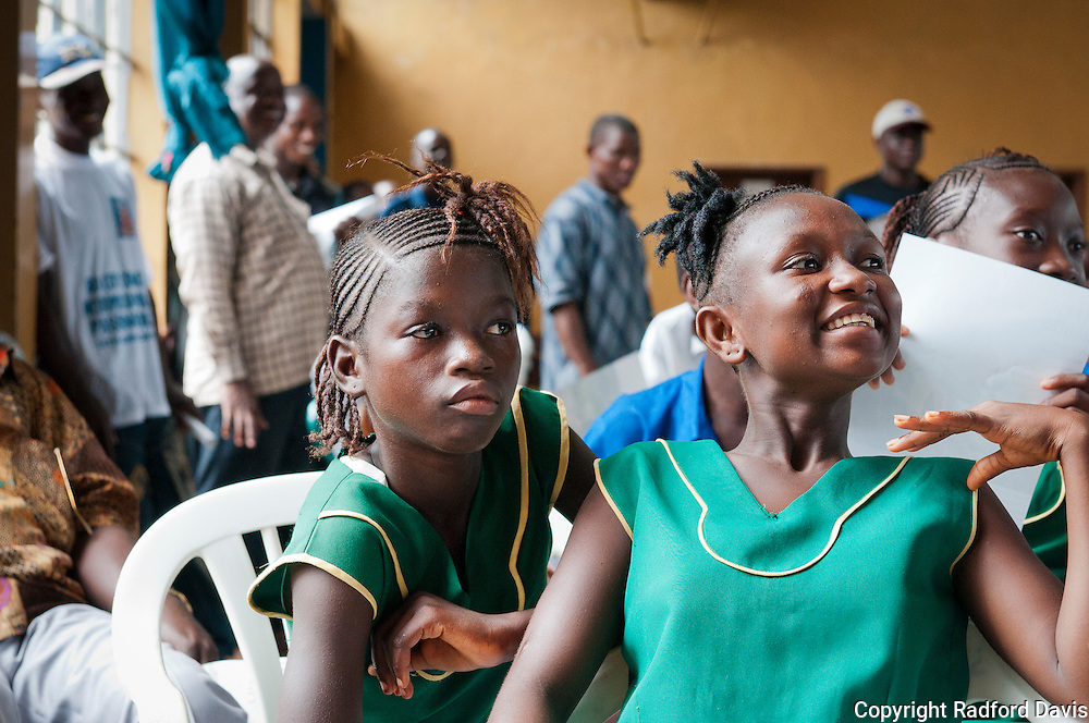 The plays, or skits, drew laughter and rapt attention from the audience. Here, two girls can't take their eyes off the stages, where a skit about rabies is taking place.