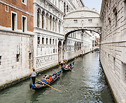 "The Bridge of Sighs (Ponte dei Sospiri, built 1602) spans the Roi di Palazzo and connects the Old Prison and interrogation rooms in the Doge's Palace to the New Prison located across the canal to the right, in Venice, Italy, Europe. The bridge can be seen from Ponte della Paglia next to the Doge's Palace. The bridge name, given by Lord Byron in the 19th century, comes from the suggestion that prisoners would sigh at their final view of beautiful Venice through the window before being taken down to their cells. In reality, the days of inquisitions and summary executions were over by the time the bridge was built and the cells under the palace roof were occupied mostly by small-time criminals. Little could be seen from inside the Bridge due to the stone grills covering the windows. A local legend says that lovers will be granted eternal love and bliss if they kiss on a gondola at sunset under the Bridge of Sighs as the bells of St Mark's Campanile toll. This legend served as a plot line for the movie ""A Little Romance,"" featuring Laurence Olivier and Diane Lane. Venice (Venezia), founded in the 400s AD, is capital of Italy's Veneto region, named for the ancient Veneti people from the 900s BC. The romantic City of Canals stretches across 100+ small islands in the marshy Venetian Lagoon along the Adriatic Sea, between the mouths of the Po and Piave Rivers. The Republic of Venice was a major maritime power during the Middle Ages and Renaissance, a staging area for the Crusades, and a major center of art and commerce (silk, grain and spice trade) from the 1200s to 1600s. The wealthy legacy of Venice stands today in a rich architecture combining Gothic, Byzantine, and Arab styles. Venice and the Venetian Lagoon are honored on UNESCO's World Heritage List."