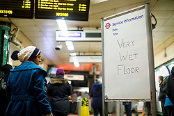 "© Licensed to London News Pictures. 12/01/2017. London, UK. A sign reads ""Very Wet Floor"" at the entrance of Camden Town tube station as people commute in north London whilst the first snow of the season starts to fall in London on Thursday, 12 January 2017. Photo credit: Tolga Akmen/LNP"