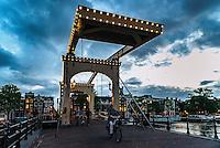 """Le Magere Brug (Pont Maigre) est un pont sur l'Amstel au centre d'Amsterdam aux Pays-Bas. Il relie les deux rives de la riviere à hauteur de la Kerkstraat, entre le Keizersgracht et le Prinsengracht. <br /> Le pont est illumine le soir par 1200 lampions.<br /> L'ouvrage d'origine fut construit en 1670, mais il etait tellement etroit que deux personnes pouvaient à peine s'y croiser. Il fut reconstruit en 1871<br /> <br /> The Magere Brug (""""Skinny Bridge"""") is a bridge over the river Amstel in the city centre of Amsterdam. It connects the banks of the river at Kerkstraat (Church Street), between Keizersgracht (Emperors' Canal) and Prinsengracht (Princes' Canal).<br /> The bridge is decorated with 1200 light bulbs that are turned on in the evening.<br /> The first bridge at this site was built in 1670 but it was very narrow, the locals called it magere brug, which literally means """"skinny bridge"""". In 1871 the state of the bridge was so bad that it was demolished and replaced by a nine-arched wooden bridge."""