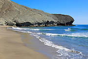 Rocky headland at Playa Monsul sandy beach, Cabo de Gata natural park, Almeria, Spain