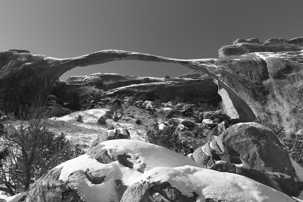 """The iconic """"Landscape Arch"""" in black and white with a few inches of fresh snow in the foreground and a light dusting remaining attached to the sandstone above ..."""