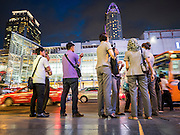 20 MAY 2015 - BANGKOK, THAILAND:   Office workers wait for a bus on Ratchadamri Road across the street from CentralWorld mall, which is lit up like this every night. Bangkok's malls consume more electricity than some provinces. Siam Paragon, a popular high end mall in central Bangkok, consumes nearly twice as much electricity at the northern province of Mae Hong Son. Thais and foreigners alike flock to the malls in Bangkok, which are air conditioned. Most of the electricity consumed in Bangkok is generated in Laos and Myanmar. In 2013, the Bangkok Metropolitan Region consumed about 40 per cent of the Thailand's electricity, even though the BMR is only 1.5 per cent of the country's land area and about 22 per cent of its population.    PHOTO BY JACK KURTZ