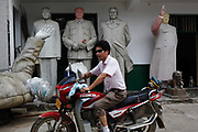"A man rides past unfinished statues of Mao Zedong at the workshop of a ""Red"" memorabilia collector and manufacturer, near Mao's birthplace in Shaoshan, Hunan Province, China on 12 August 2009. The village of Shaoshan, in rural Hunan Province, is tiny in size but big in name. It was the childhood home for Mao Zedong, the controversial revolutionary who came from obscurity but eventually defied all odds conquered China in the name of communism. Now his home, a sacred place among China's official propaganda, is in reality a microcosm of the country itself: part commercialism, part superstition, with a dash of communist ideological flavor."