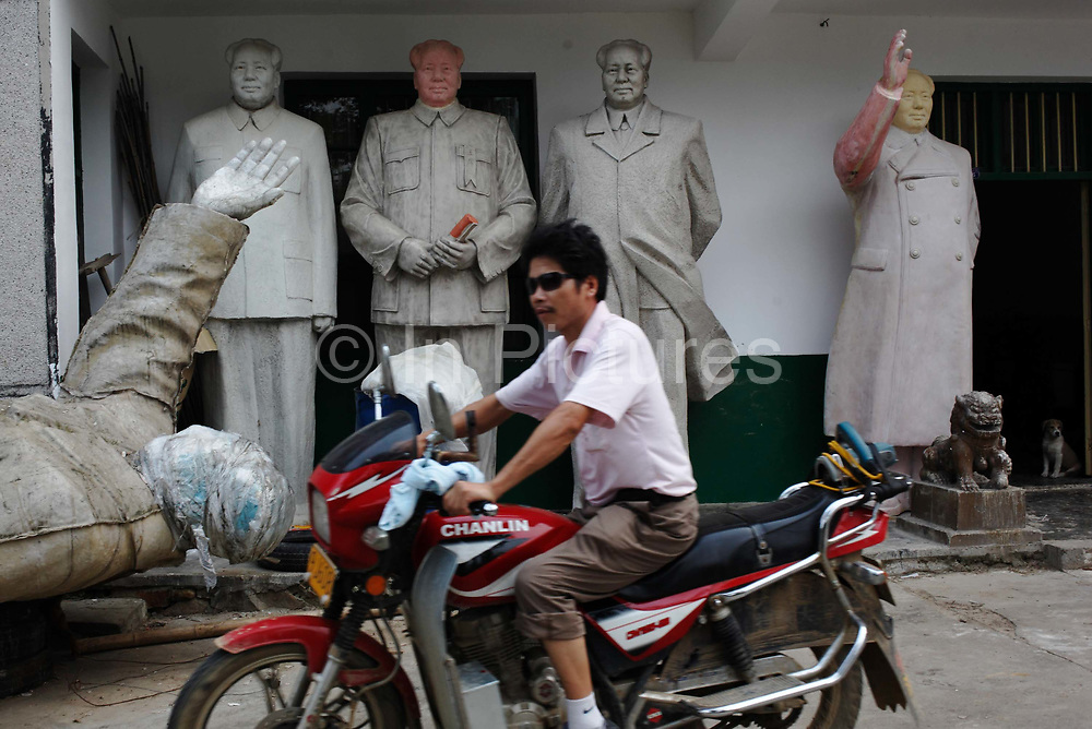 """A man rides past unfinished statues of Mao Zedong at the workshop of a """"Red"""" memorabilia collector and manufacturer, near Mao's birthplace in Shaoshan, Hunan Province, China on 12 August 2009. The village of Shaoshan, in rural Hunan Province, is tiny in size but big in name. It was the childhood home for Mao Zedong, the controversial revolutionary who came from obscurity but eventually defied all odds conquered China in the name of communism. Now his home, a sacred place among China's official propaganda, is in reality a microcosm of the country itself: part commercialism, part superstition, with a dash of communist ideological flavor."""