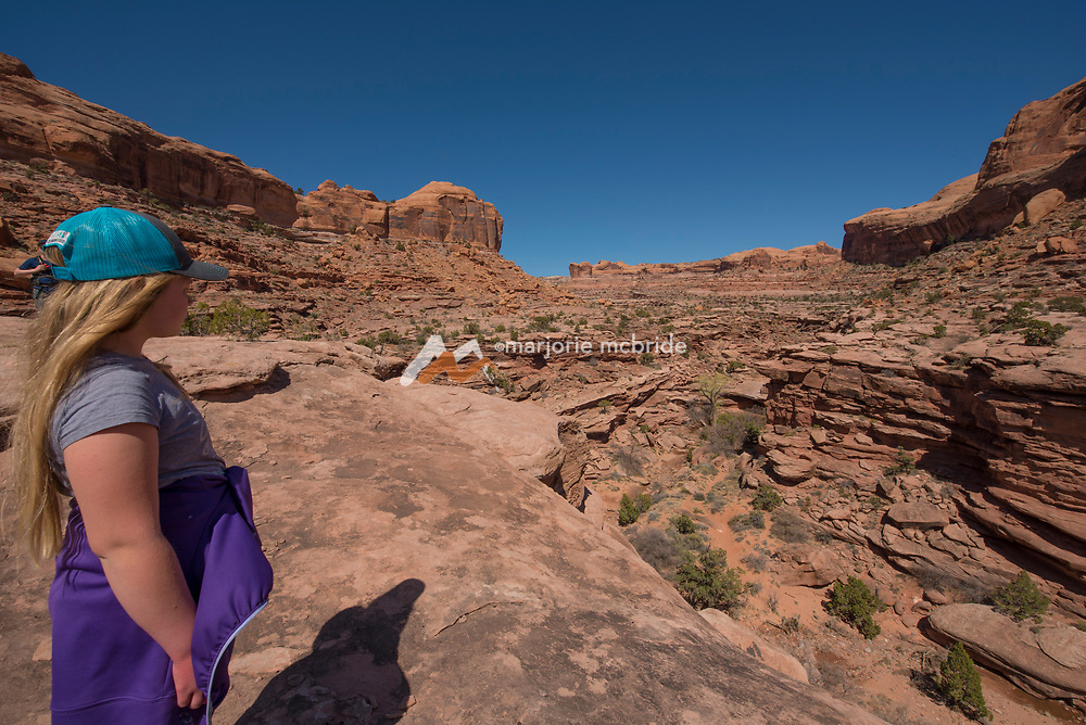 Girl taking in the view on hikt to Jeep Arch, Moab, Utah.