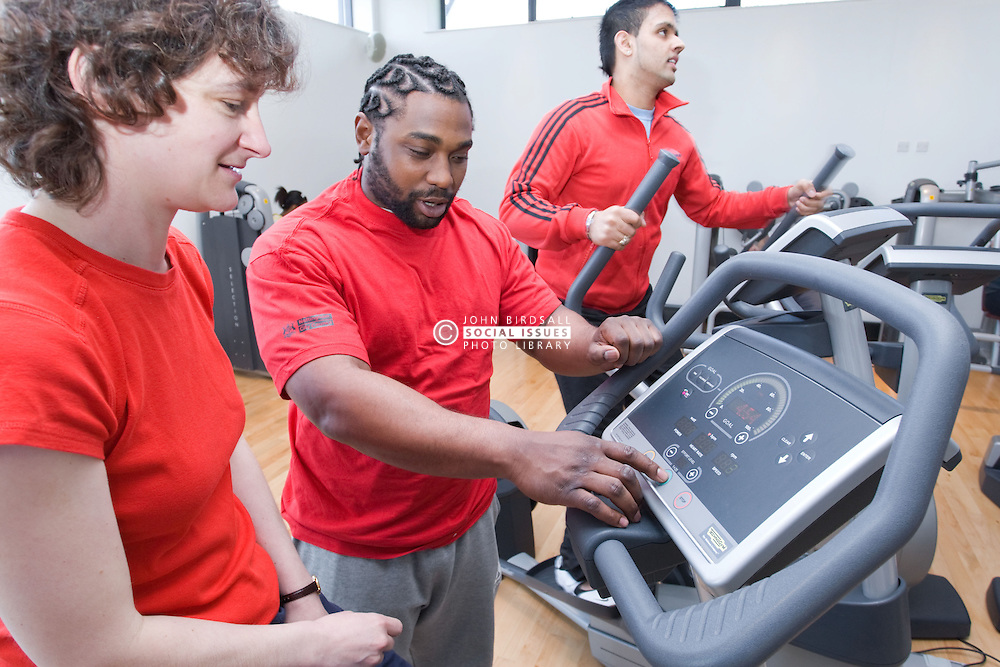 Fitness instructor showing woman how to use the exercise bike at her sports leisure centre,