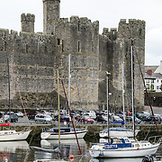 Part of the formidable defensive outside walls at Caernarfon Castle in northwest Wales. A castle originally stood on the site dating back to the late 11th century, but in the late 13th century King Edward I commissioned a new structure that stands to this day. It has distinctive towers and is one of the best preserved of the series of castles Edward I commissioned.