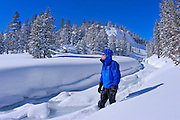 Backcountry skier in fresh snow along frozen Lee Vining Creek, Inyo National Forest, Sierra Nevada Mountains, California