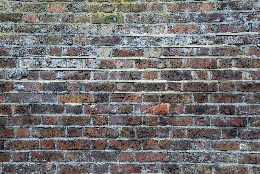 Old bricks on a building in London show many years of weathered wear over time