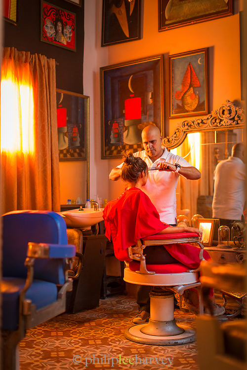 Man cutting woman hair in hair saloon, Havana, Cuba