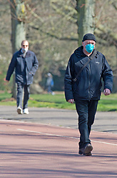 ©Licensed to London News Pictures 26/03/2020<br /> Greenwich, UK. Walkers with protective masks on. People get out and about in Greenwich Park, Greenwich, London this afternoon as they make the most of their permitted one a day exercise out of the house from Coronavirus Lockdown. The Prime Minister Boris Johnson has asked people to stay at home to help in the fight against Covid-19. Photo credit: Grant Falvey/LNP