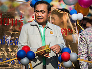 09 JANUARY 2016 - BANGKOK, THAILAND:     PRAYUTH CHAN-O-CHA, the Prime Minister of Thailand, cuts the ribbon to open Children's Day festivities at Government House. National Children's Day falls on the second Saturday of the year. Thai government agencies sponsor child friendly events and the military usually opens army bases to children, who come to play on tanks and artillery pieces. This year Thai Prime Minister General Prayuth Chan-ocha, hosted several events at Government House, the Prime Minister's office.    PHOTO BY JACK KURTZ