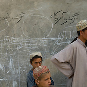 """Afghan civilians stand by a wall covered in graffiti depicting machine guns and two anti-colaition slogans in Pashto saying """"Death for London"""" and Death for America"""" in an area recently pacified and secured by the US Marines from the 24th Marine Expeditionary Unit (MEU) and British Forces in Garmsir District, Helmand Province, Afghanistan. Garmsir has been a haven for insurgents for the last several years. Earlier this year the Marines cleared the area after a period of heavy fighting and recently handed over control to British Forces."""