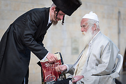 19 April 2019, Jerusalem: A young Jewish man gives money to an old man by the Western Wall in Jerusalem. On the first day of Pesach (Passover) Jews gather to pray by the Western Wall in Jerusalem, considered as the most sacred and holy place for the Jews.