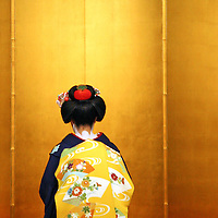 Asia, Japan, Kyoto. A geisha kneels before beginning a traditional dance performance.