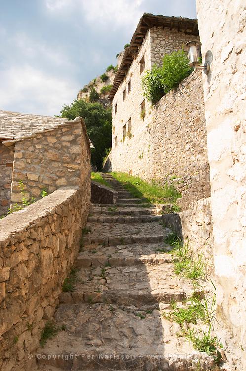 Narrow cobble stone street leading up to the tower fortress. Pocitelj historic Muslim and Christian village near Mostar. Federation Bosne i Hercegovine. Bosnia Herzegovina, Europe.