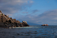 Tourists explore the sea cliffs of Isabela Island by zodiac in the Galapagos National Park, Galapagos, Ecuador, South America