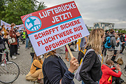 """A protester holds a banner as people take part in a demonstration in front the Reichstag  building, seat of the German lower house of Parliament, the Bundestag in Berlin, Germany, August 17, 2021. About 1000 people gathered in front of the  under the call """"Airlift now! Create safe escape routes from Afghanistan!"""", the spontaneous event was organized by Seebrücke and several other human-rights organizations."""