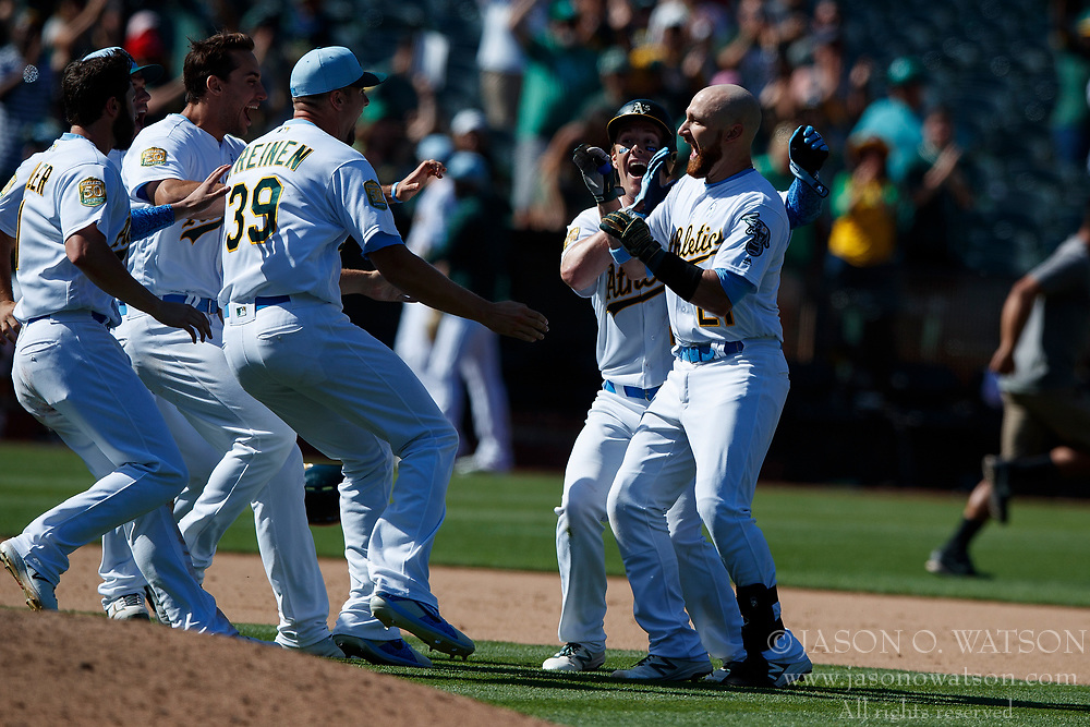 OAKLAND, CA - JUNE 17: Jonathan Lucroy #21 of the Oakland Athletics is congratulated by teammates after hitting a walk off RBI single against the Los Angeles Angels of Anaheim during the eleventh inning at the Oakland Coliseum on June 17, 2018 in Oakland, California. The Oakland Athletics defeated the Los Angeles Angels of Anaheim 6-5 in 11 innings. (Photo by Jason O. Watson/Getty Images) *** Local Caption *** Jonathan Lucroy