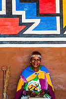 Woman in traditional costume, Lesedi Cultural Village, Broederstroom (near Johannesburg), South Africa. The cultural village includes five traditional homesteads, each inhabited by Zulu, Xhosa, Pedi, Basotho and Ndebele tribes who live according to tribal folklore and traditions of their ancestors.