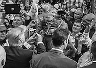 Baton Rouge, LA, Republican presidential candidate Donald Trump at a campaign rally, signs the hand of 19 month old Curtis Ray Jeffrey II, of Bluff Creek, La., a baby model whose hair is worn to mimic Trumps.