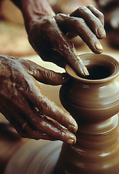 Asia, India, Rajasthan, Udaipur, hands sculpting clay urn on potter's wheel