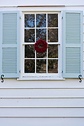 A low country popcorn berry Christmas wreath hangs from a window on a historic home along King Street in Charleston, SC.