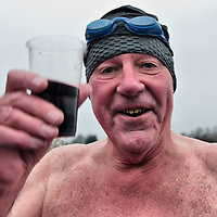 LONDON, ENGLAND - DECEMBER 25:  A member of the Serpentine Swimming Club toasts after swimming in the icy Serpentine waters during the annual Christmas Day Peter Pan Cup on December 25, 2009 in London, England.  The traditional 100 yards Christmas race got its name in 1904 after Sir James Barrie presented the first Peter Pan Cup and is only open to club members who have competed in at least three of the winter series races.   (Photo by Marco Secchi/Getty Images)