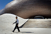 A boy walks near the newly constructed Ordos Museum, which was designed by Chinese architect Ma Yansong. The museum is located in the new city centre of the new town. Driven by a booming economy, the Municipal Government was determined to create this new city, dozens of kilometers away from the current city, on a site that until recently was nothing but the Gobi Desert.