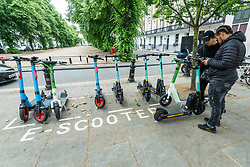 © Licensed to London News Pictures. 22/06/2021. LONDON, UK.  Riders return their rental e scooters to a designated parking area on the King's Road in Chelsea.  These form part of a trial e scooter rental scheme launched on Monday 7 June, running for an initial 12 months, allowing pedestrians to hire an dride them legally, but only in certain boroughs of the capital as long as the regulations are observed.  By contrast, privately owned e scooters, although popular for many, remain illegal on public roads and pavements.  Photo credit: Stephen Chung/LNP