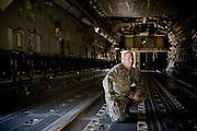Technical Sgt. Kurt Hollensteiner kneels inside a C-17 Globemaster aircraft under maintenance by the 315th Aircraft Maintenance at Charleston Charleston Air Force Base, S.C., on Oct. 30, 2008.
