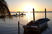 Caye Caulker island ocean view, boats and jetee at dusk, silhouettes and afternon light. Belize.