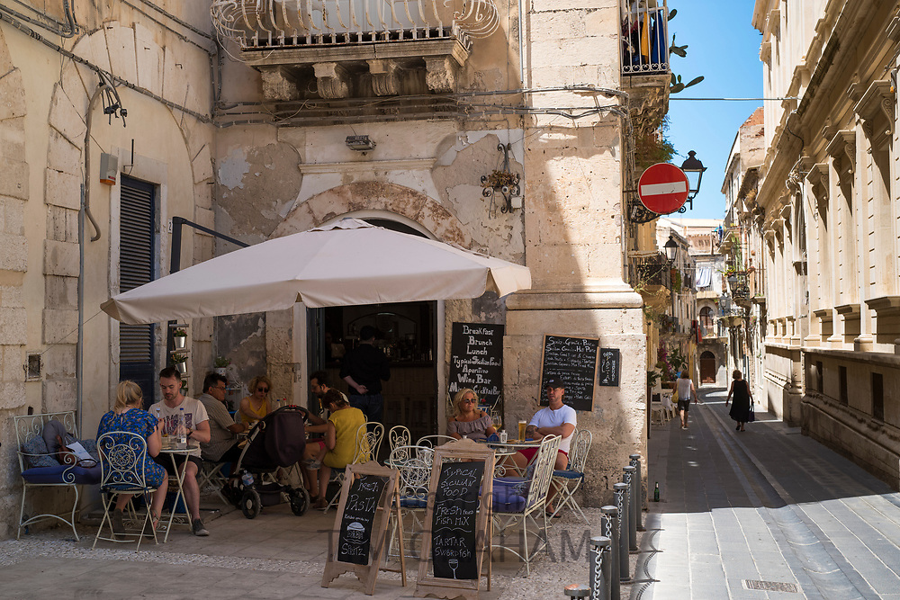 Cafe culture - locals and tourists dining at Cafe  on via Della Maestranza in Ortigia, Sicily, Italy