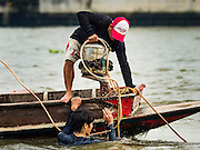 06 OCTOBER 2015 - BANGKOK, THAILAND:  A spotter lifts the dive helmet off of a diver surfacing from the bottom of the Chao Phraya River in Bangkok. Divers work in two man teams on small boats in the Chao Phraya River. One person stays in the boat while the diver scours the river bottom for anything that can be salvaged and resold. The divers usually work close to shore because the center of the river is a busy commercial waterway with passenger boats and commercial freight barges passing up and down the river all day long. The Chao Phraya is a dangerous river to dive in. It's deep, has large tidal fluctuations, is fast flowing and badly polluted. The divers make money only when they sell something.    PHOTO BY JACK KURTZ