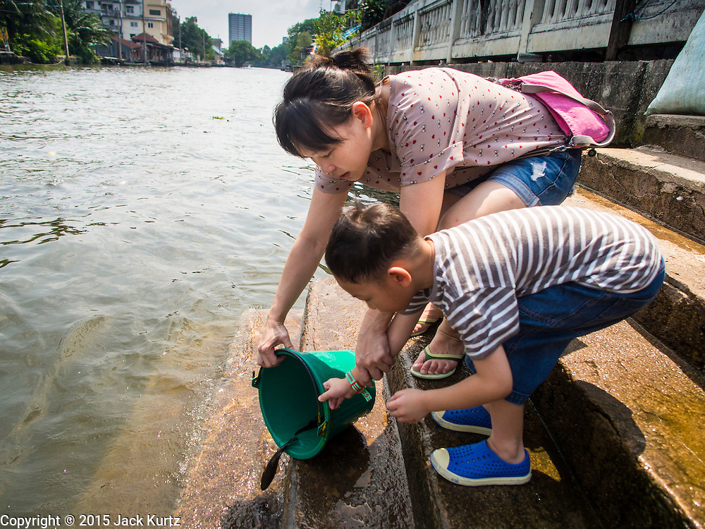 20 APRIL 2015 - BANGKOK, THAILAND:   A Buddhist woman and her son release fish into Khlong Bangkok Yai in the Thonburi section of Bangkok. Releasing animals, frequently small birds buy also fish and reptiles, is a common way of making merit in Buddhist countries.   PHOTO BY JACK KURTZ