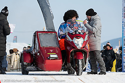 Moscow motorcycle mechanic Alexander Pikalo who rode the 6,000 km from Moscow to Baikal at the Baikal Mile Ice Speed Festival opening ceremonies where participants on the big stage were introduced to the crowd one at a time. Maksimiha, Siberia, Russia. Saturday, February 29, 2020. Photography ©2020 Michael Lichter.
