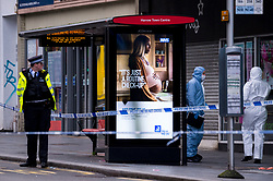© Licensed to London News Pictures. 14/12/2020. HARROW, UK. Forensics officers in Station Road. A man, believed to be in his 20s, has died and two others, believed to be in their late-teens, have been injured in a stabbing Station Road in Harrow, north west London. The Met Police said emergency services were called to the area at 19:15 GMT on Sunday 13 December to reports of a stabbing.  A crime scene remains in place.  Photo credit: Stephen Chung/LNP