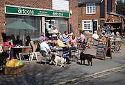 People sitting outside the art cafe, West Mersea village, Mersea Island, Essex, England