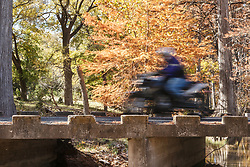 Motorcycle crossing Cypress Creek bridge in Autumn, near Comfort, Texas USA