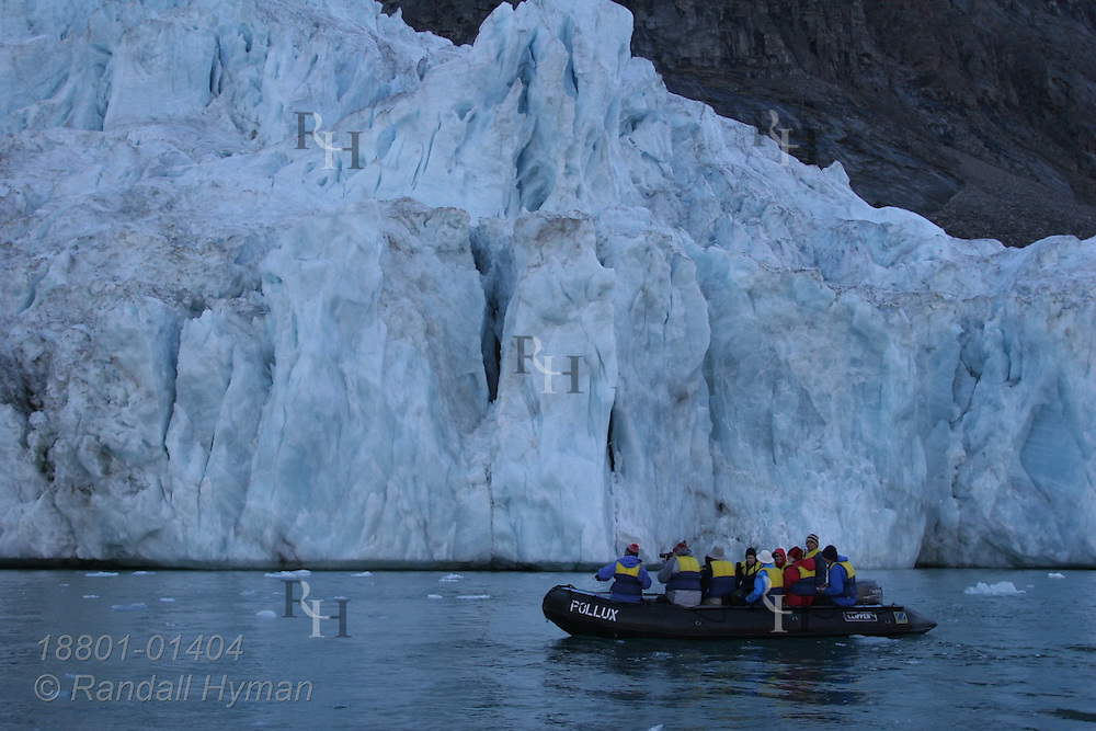Clipper Adventurer cruise ship passengers in Zodiac raft pass foot of glacier in Dexterity Fjord, Baffin Island; Nunavut, Canada