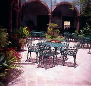 A294HB Table and chairs in hotel courtyard garden Mexico