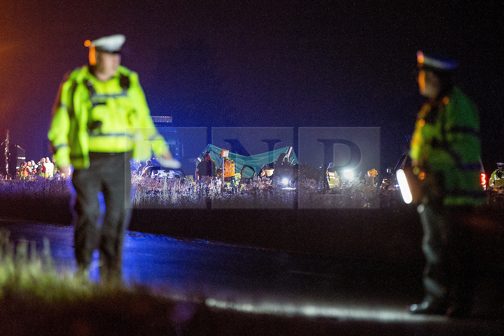 © Licensed to London News Pictures . 21/07/2014 . Nottinghamshire , UK . Police scour the slip road for evidence . Police , fire crew and ambulances on the A1 road in Ranby yesterday morning (21st July 2014) following a fatal multi vehicle accident . Leroy and Sheila Carrington (aged 68 and 58) died at the scene when the Peugot 206 they were driving collided with a Vauxhall Astra . Roderick Franks (58) , who was a passenger in the Astra , died in hospital , following the crash . The road was closed in both directions whilst police investigated the scene .  Photo credit : Joel Goodman/LNP