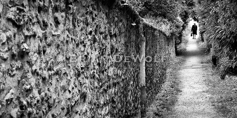 The path behind the houses is worn from bicyclists and pedestrians.  Little gates allow entry into the back yards. The woman with her shopping bag takes the path home from the village of Louveciennes, France. Digital capture.   Aspect Ratio 1w x 0.5h